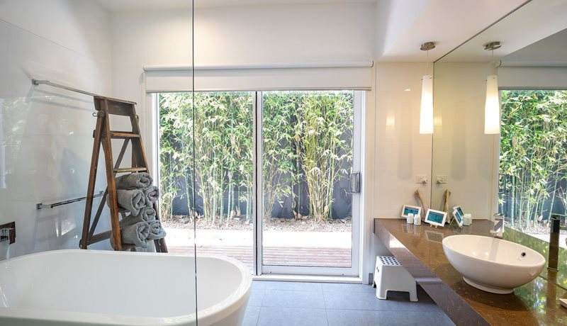 Indulge in a luxury deep bath overlooking a private space.