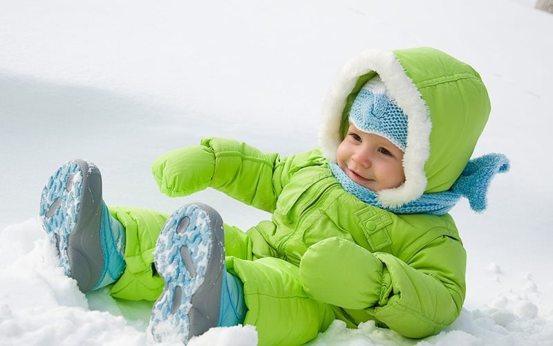 A toddler with a green snowsuit on in the snow