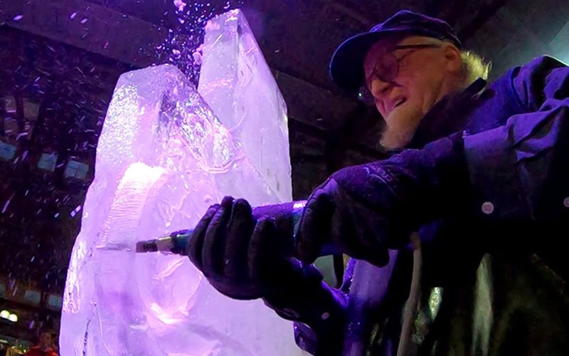 Man carving a sculpture from ice