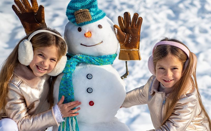 two children posing with a snowman